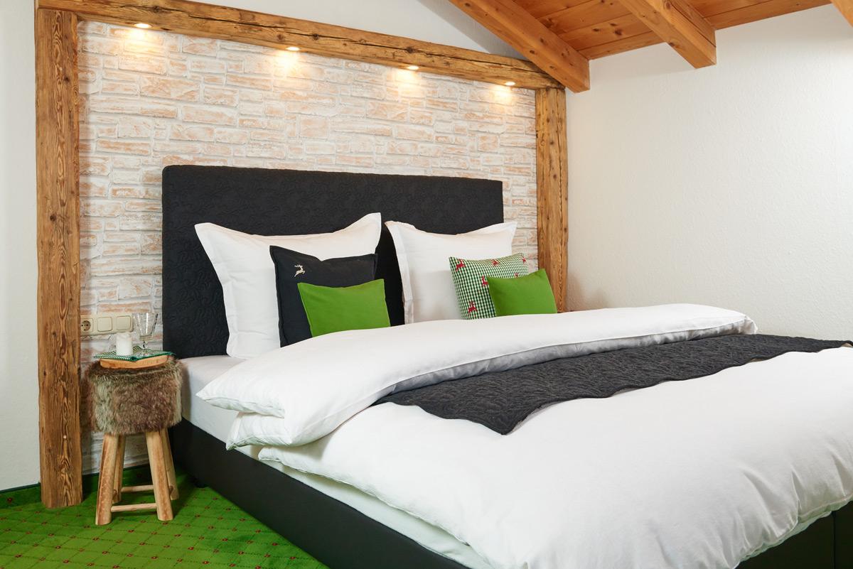 Alpglück Bett mit grüner Bettwäsche passend zum grünen Fußboden