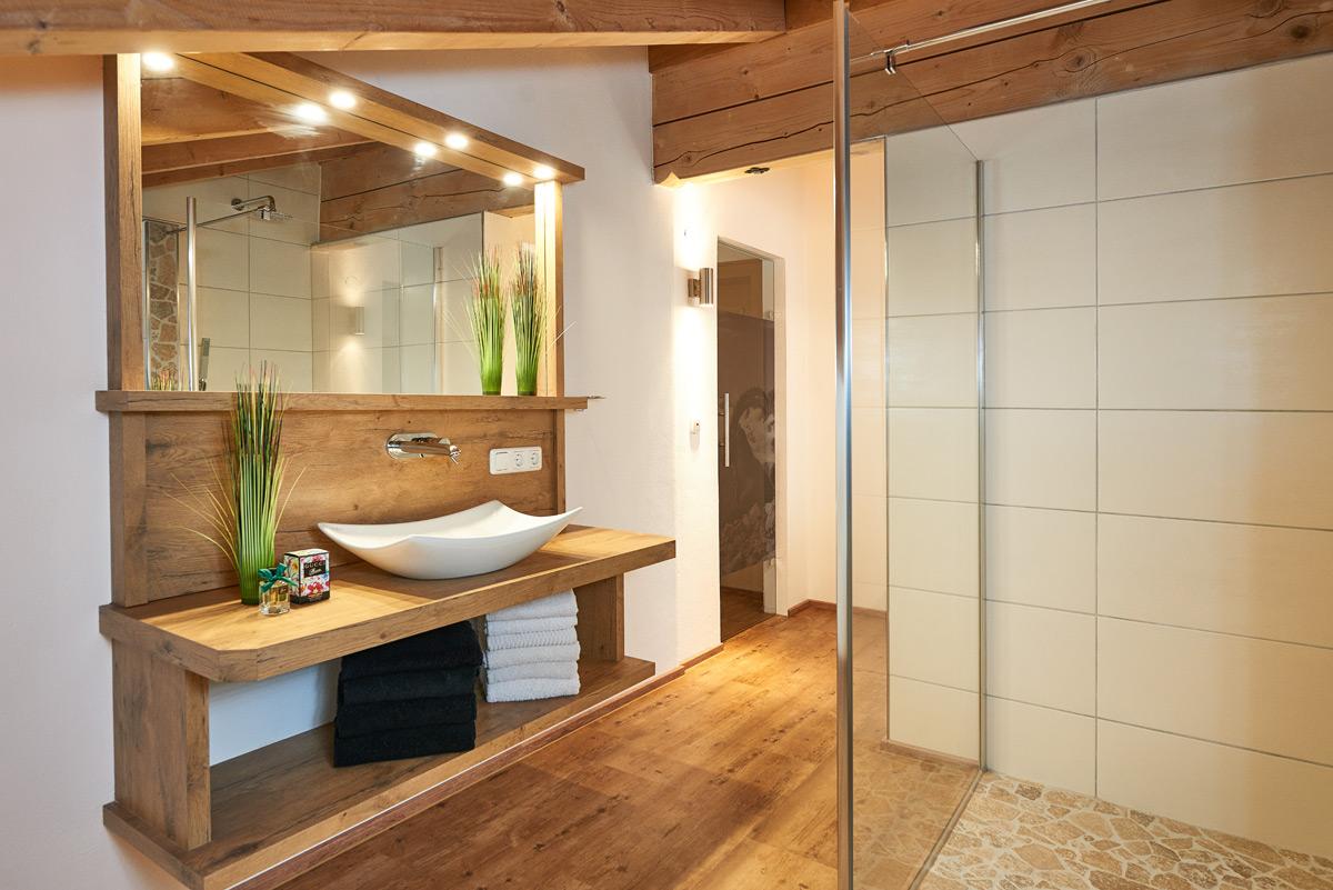 Alpglück Badezimmer mit Holzboden und Holzschrank sowie geräumiger Dusche und Waschbecken