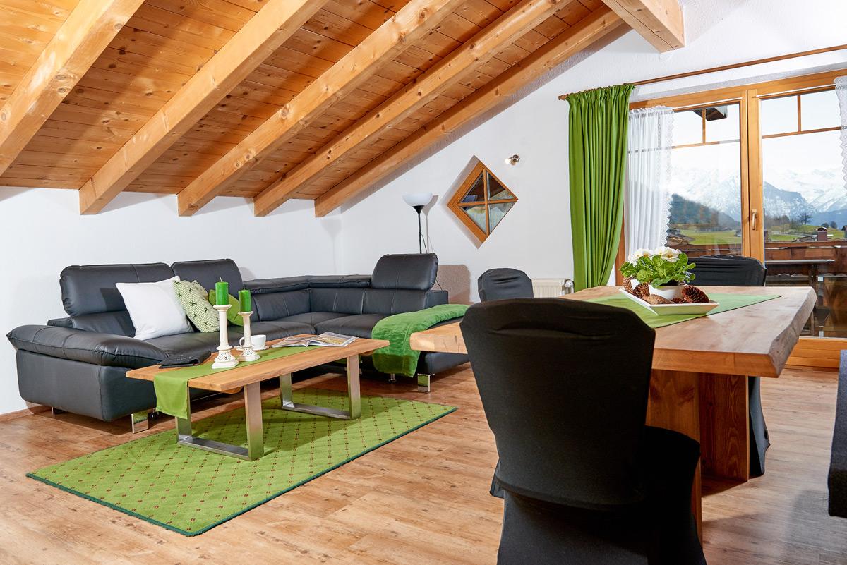 Alpglück Wohnzimmer mit Esstisch und Couch und grünen Akzenten durch Gardinen, Teppich und Tischläufer