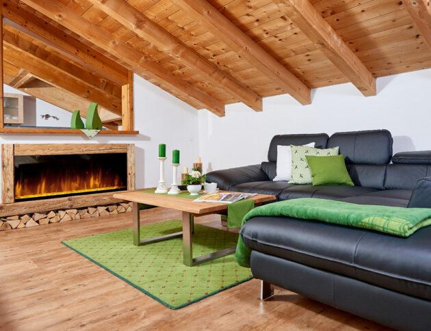 Alpglück Wohnzimmer mit Couch, Couchtisch und Kamin sowie grünen Akzenten durch Kerzen, Decke und Teppich