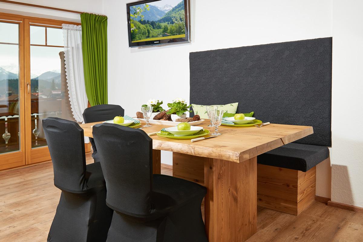 Alpglück Essbereich mit Holztisch, einer Bank und zwei Stühlen