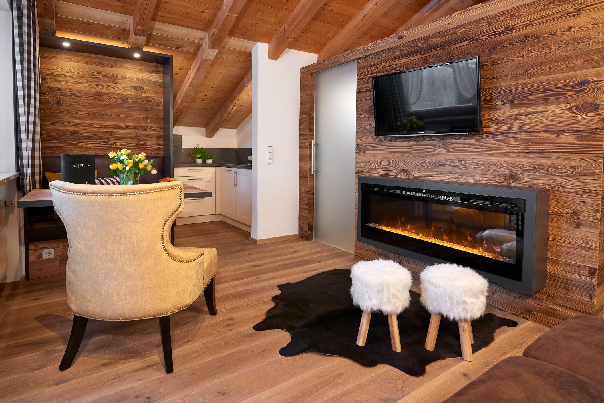 Alpkitz Wohnzimmer mit Kaminfeuer und Sessel sowie zwei Hockern