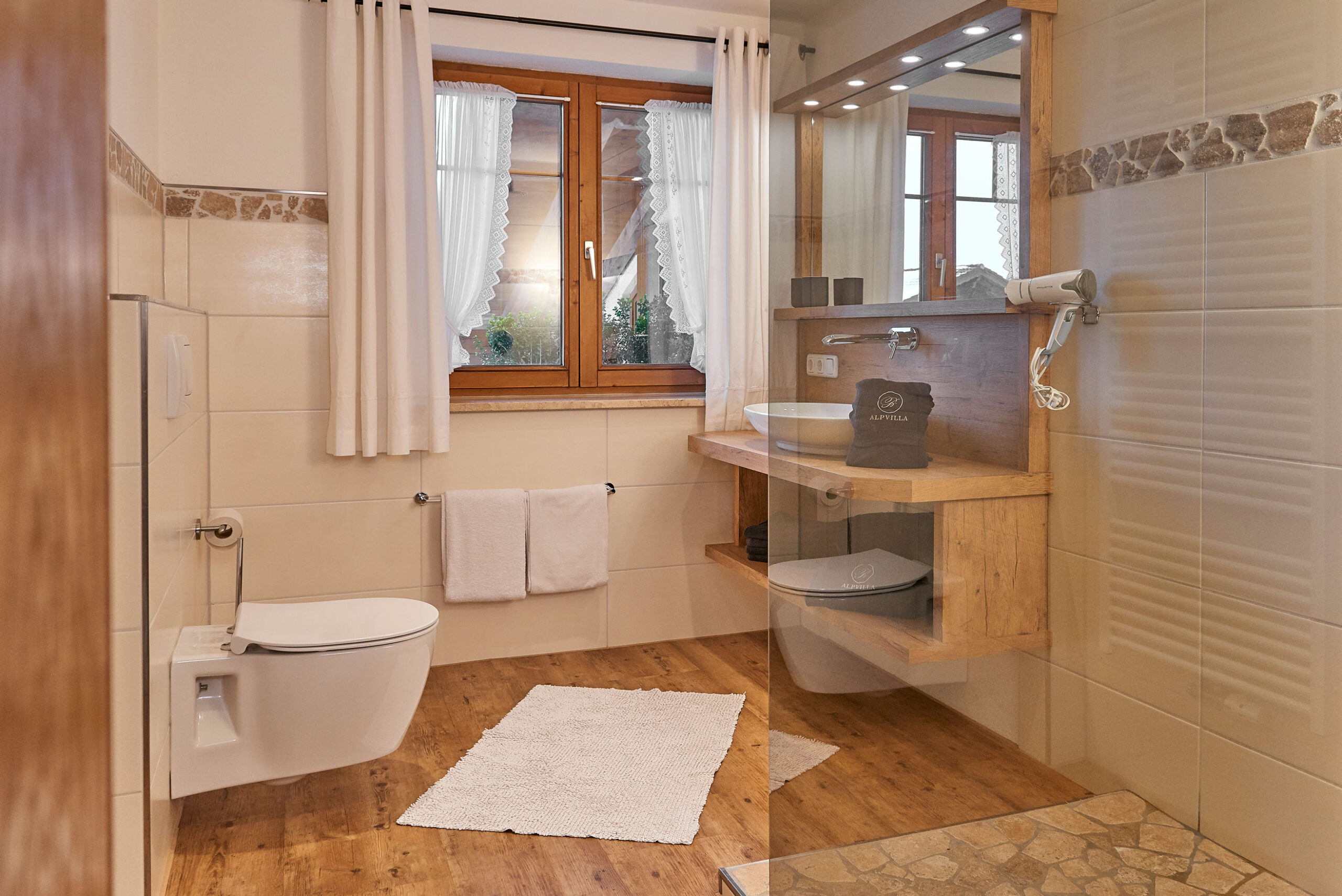 Badezimmer mit Holzboden und Holzschrank