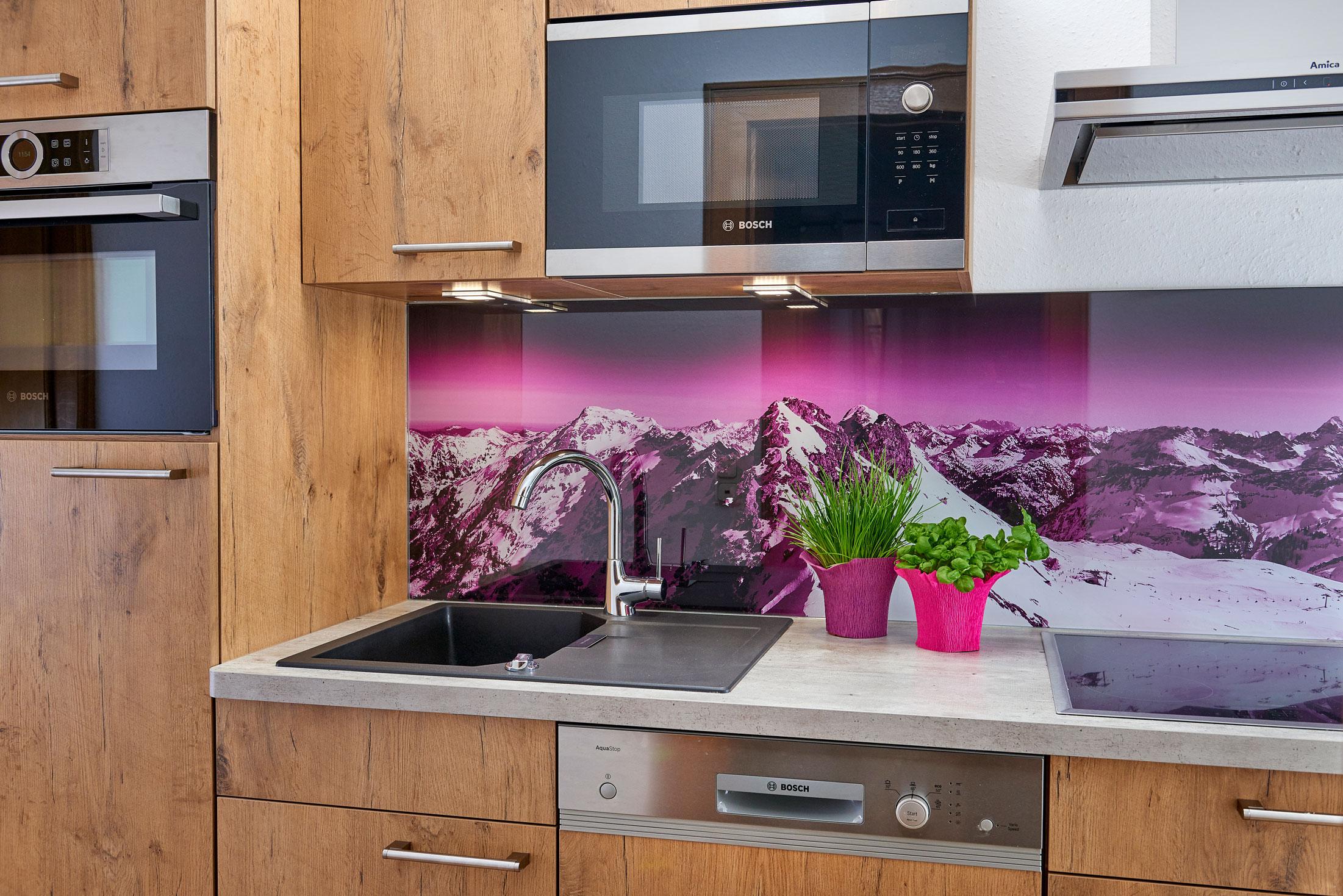 Küchenzeile aus Holz und pinkem Alpenpanorama als Spritzschutz