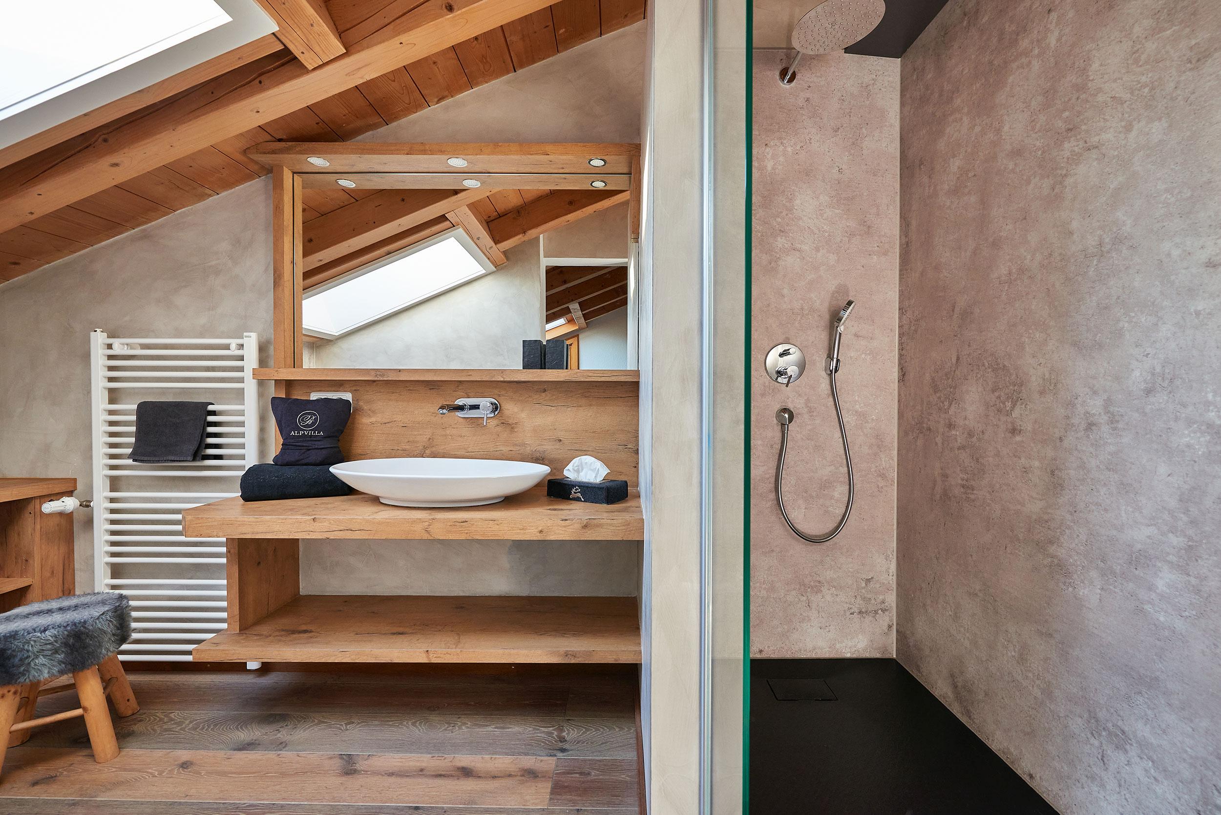 """Badezimmer """"Almrausch"""" mit Waschbecken und großem Spiegel auf der linken Seite und Dusche auf der rechten Seite getrennt durch eine Glaswand."""
