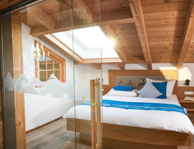 Schlafzimmer mit Holzbett und Dachfenster sowie einer Glastüre