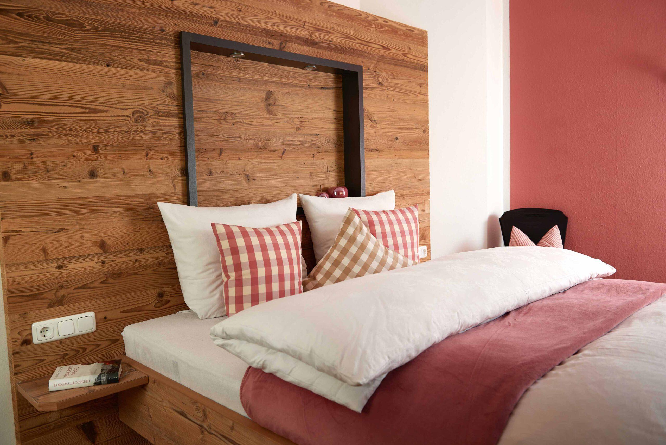 Holzbett mit großem Holz-Kopfteil und rot-weißer Bettwäsche