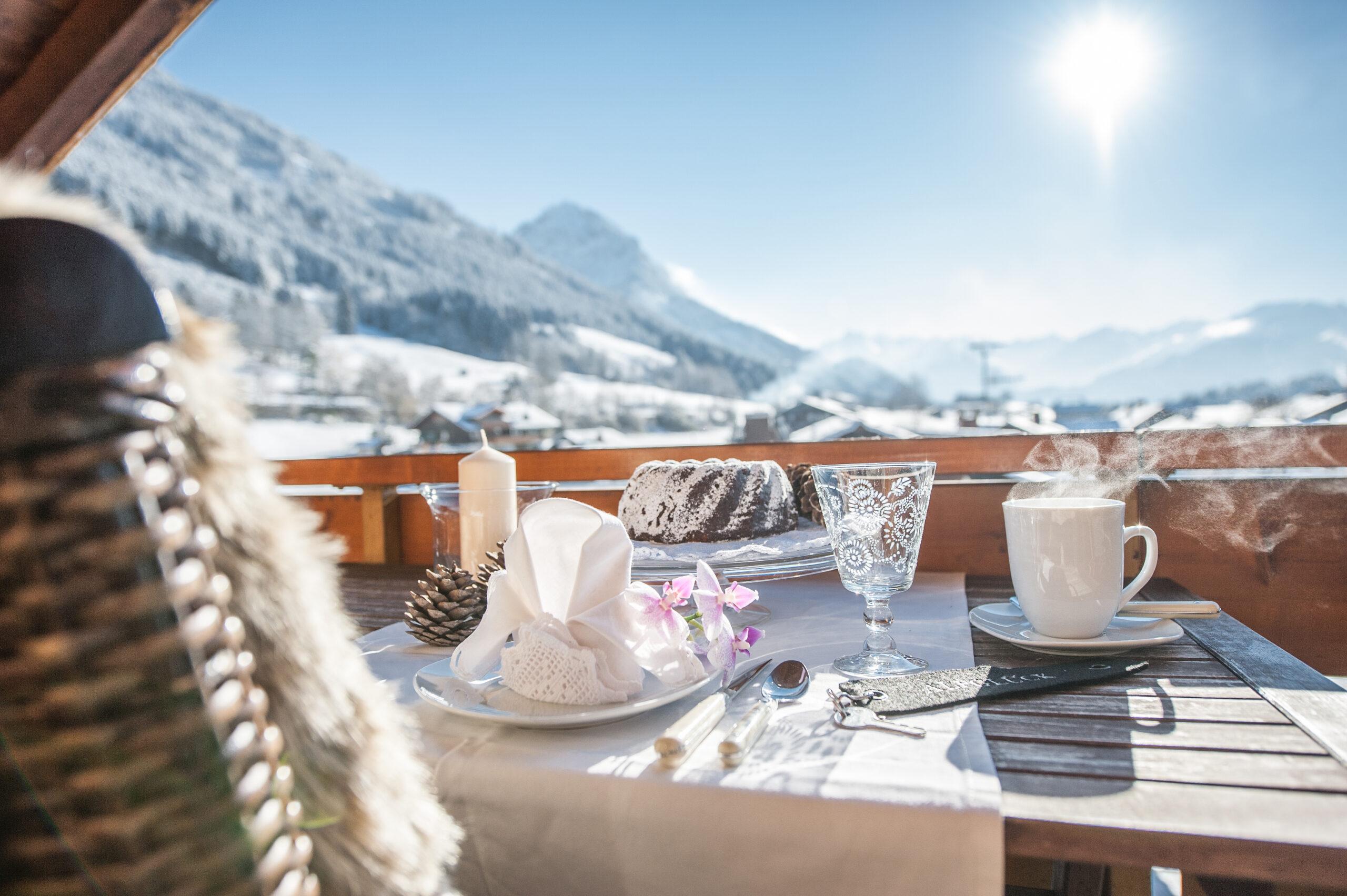 gedeckter Esstisch auf Balkon im Winter bei Sonnenschein